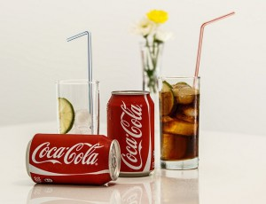 Coca-Cola cans and glass of Coke Ice and Straw