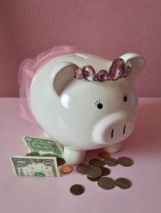 Piggy bank with paper and coin currency