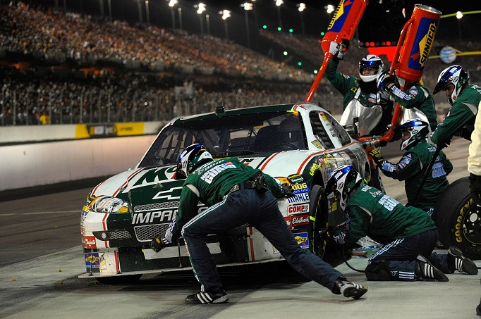 The Pit Crew of a NASCAR driver franticly changes tires and refuels the car