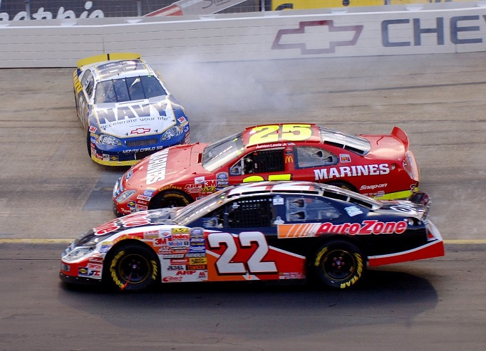 A NASCAR car loses control and skidding sideways as other cars pass by
