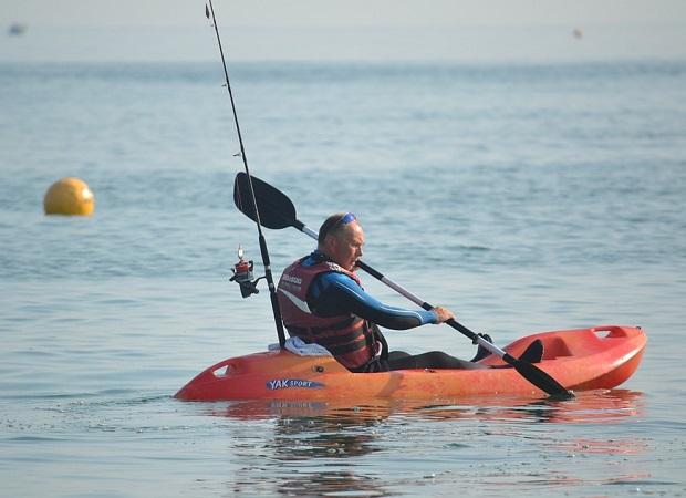 man in his fishing kayak paddling out in the ocean